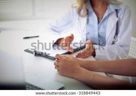 Doctor and patient are discussing something, just hands at the table - stock photo