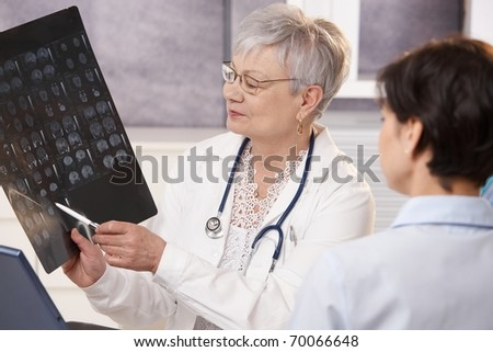 Doctor and patient discussing x-ray results in doctor's office.? - stock photo