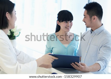 Doctor and smiling couple standing by the counter in the hospital  - stock photo