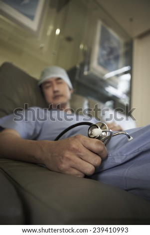 Doctor Asleep Holding Stethoscope - stock photo