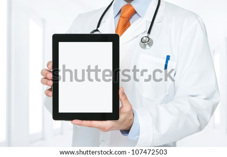 Doctor at hospital holding blank digital tablet with clipping path for the screen - stock photo