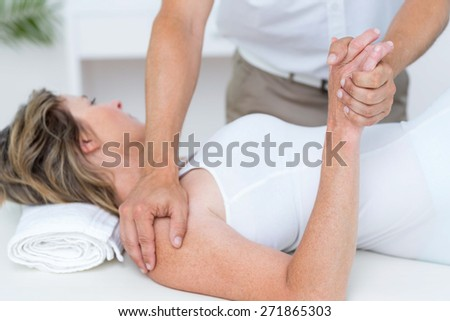 Doctor bending his patient arm in medical office - stock photo
