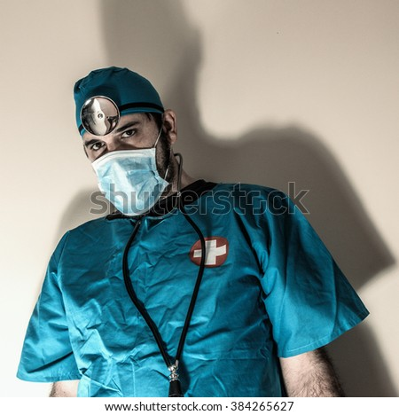 Doctor Blue Scrubs. Physician wearing blue scrubs, glasses and wearing head mirror with shadow. - stock photo