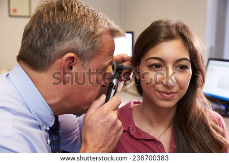 Doctor Carrying Out Ear Exam On Female Patient - stock photo