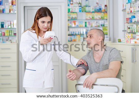 Doctor checking blood pressure of a male patient - stock photo