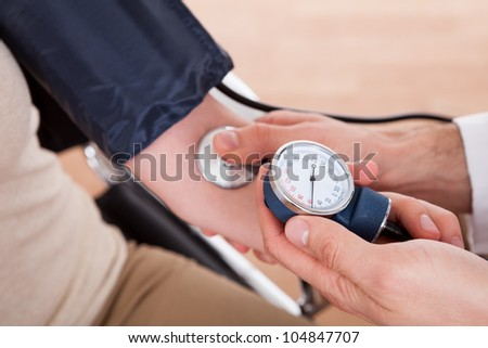 Doctor checking blood pressure of a woman. Close-up shot - stock photo