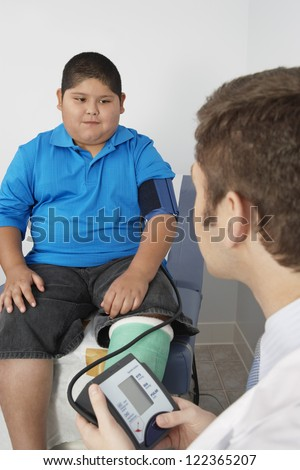 Doctor checking blood pressure of boy with fractured leg - stock photo