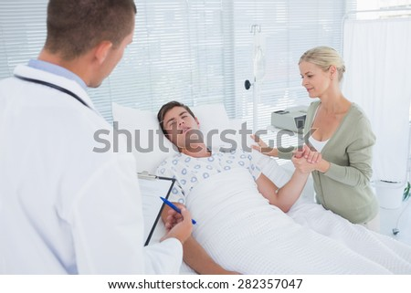 Doctor checking his patient in hospital room - stock photo
