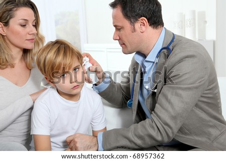 Doctor checking little boy's ear infection - stock photo