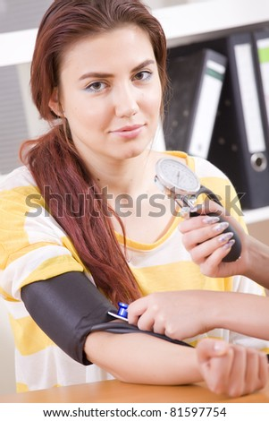 doctor checking the blood pressure of a female patient - stock photo