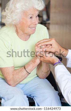 Doctor comforting happy senior woman - stock photo