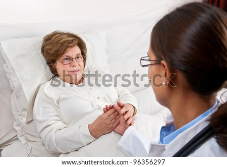 Doctor comforting senior patient - stock photo
