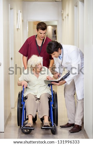 Doctor communicating with disabled senior female patient in hospital corridor - stock photo