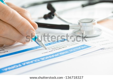 Doctor completing a Medical Claim Form by Stethoscope  - stock photo