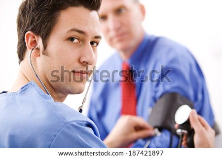 Doctor: Confident Male Nurse Takes Blood Pressure - stock photo