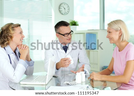 Doctor describing vitamins to patient at medical consultation - stock photo