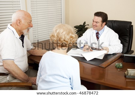 Doctor discussing treatment options with an elderly couple in his office. - stock photo
