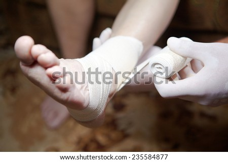 Doctor doing a bandage for patient. First aid - stock photo
