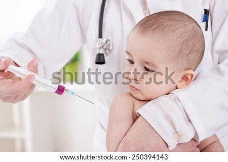 Doctor doing vaccine to little baby boy - stock photo