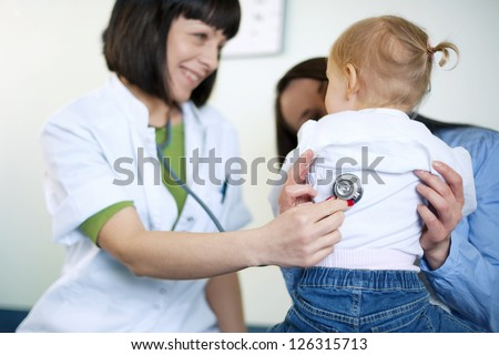 Doctor examining a little girl - stock photo