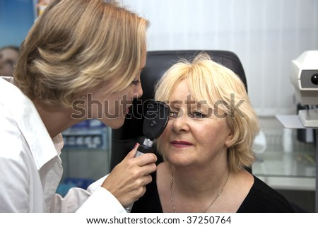 doctor,examining a patient in ophthalmology laboratory - stock photo