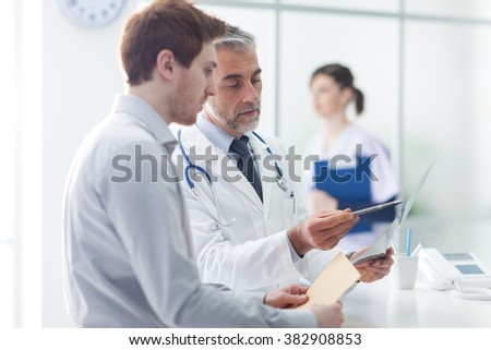 Doctor examining an x-ray and pointing, the patient is listening and watching, healthcare concept - stock photo