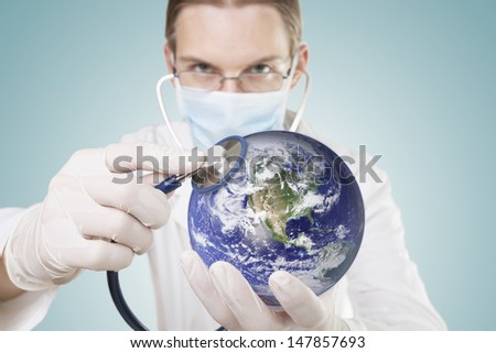 Doctor examining health of our planet. Symbol of care for environment or global economy. Elements of this image furnished by NASA. - stock photo