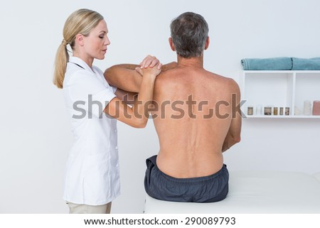 Doctor examining her patient shoulder in medical office - stock photo
