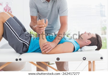 Doctor examining his patient arm in medical office - stock photo