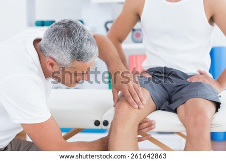 Doctor examining his patient knee in medical office - stock photo