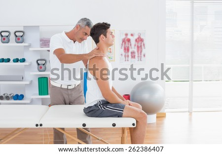 Doctor examining his patient neck in medical office - stock photo