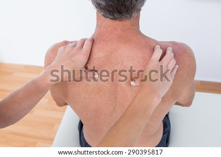 Doctor examining his patient shoulder in medical office - stock photo