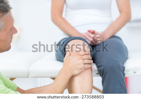 Doctor examining his patients knee in medical office - stock photo