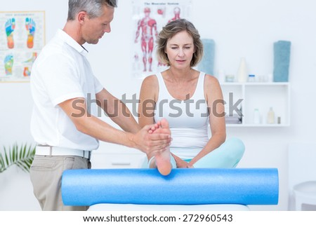 Doctor examining his patients leg in medical office - stock photo