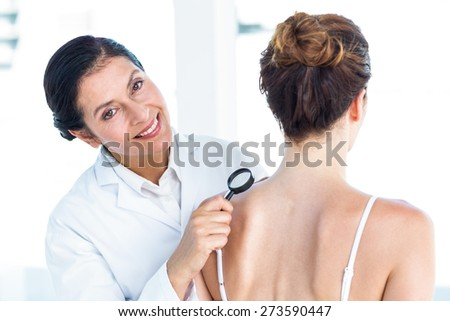 Doctor examining patient with magnifying glass in medical office - stock photo