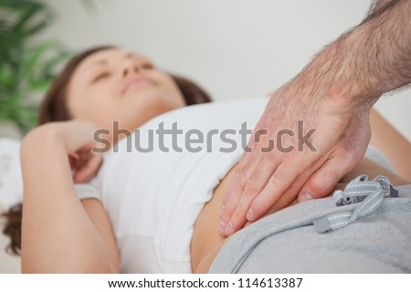 Doctor examining the stomach of his patient in a room - stock photo