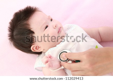 Doctor exams baby with stethoscope - stock photo