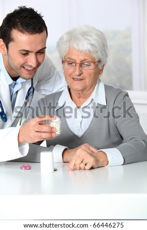 Doctor explaining drugs prescription to elderly woman - stock photo