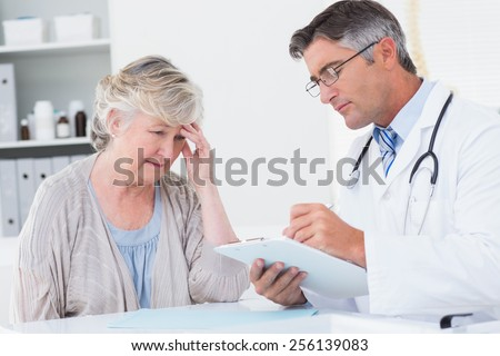 Doctor explaining prescription to senior female patient in clinic - stock photo