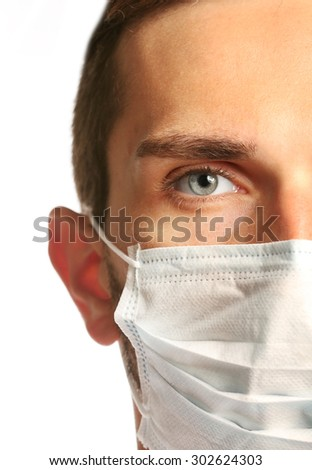 Doctor face in medical mask on grey background - stock photo