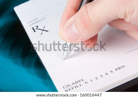 Doctor filling in empty medical prescription on Xray photo of lungs  - stock photo