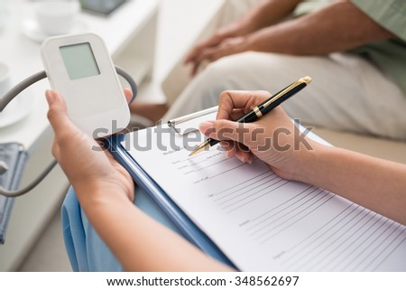Doctor filling medical card with information about the patient - stock photo