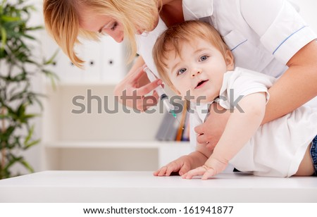 Doctor giving a child a huge injection in arm - stock photo