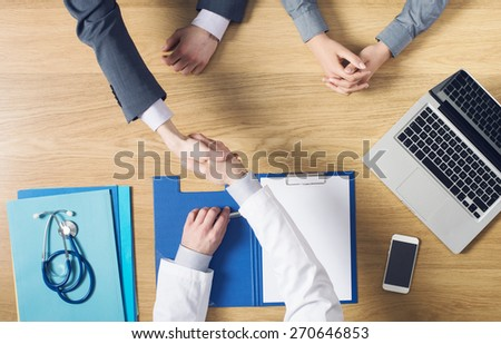 Doctor giving an handshake to his patient while sitting at his desk during a visit, trust and satisfaction concept - stock photo