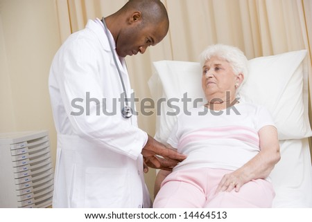 Doctor giving checkup to woman in exam room - stock photo