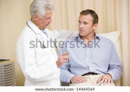 Doctor giving man checkup in exam room - stock photo