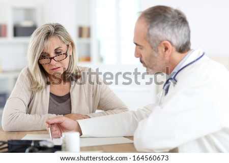 Doctor giving medicine to senior woman for arthritis pain - stock photo