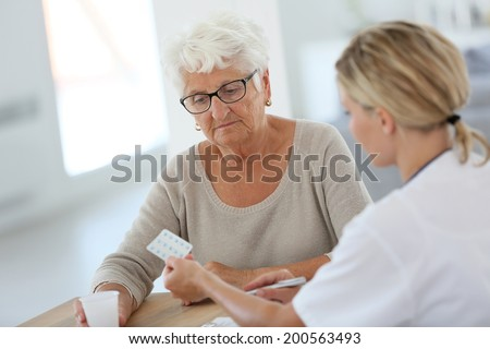 Doctor giving pills to elderly woman - stock photo