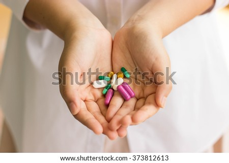 doctor hand holding a lot of medicine pills - stock photo