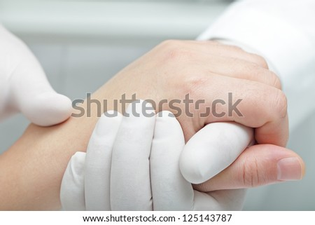 Doctor hand touches and holds the hand of the patient - stock photo